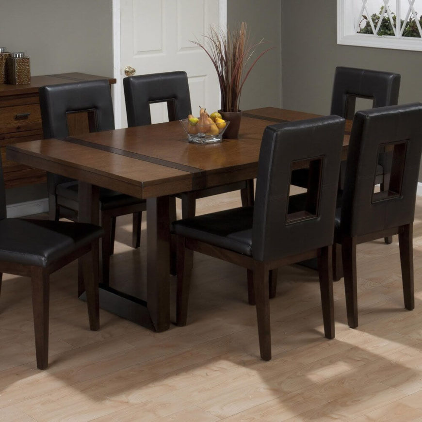 We begin with a unique table, framed with a pair of open rectangular legs that are mirrored on the surface with a strip of darker shaded wood. This angular look goes well with the boxy, leather upholstered chairs seen in the image.