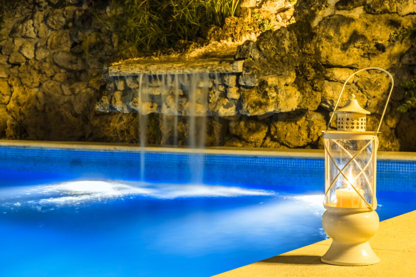 A lighted rock waterfall with a smooth outcropping to gently cascade down into the pool.