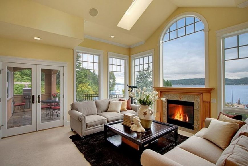 Large windows share an amazing view with this soft yellow living room. The skylights pull light into the room to accent the front of the room, where the exquisite mantle lays.