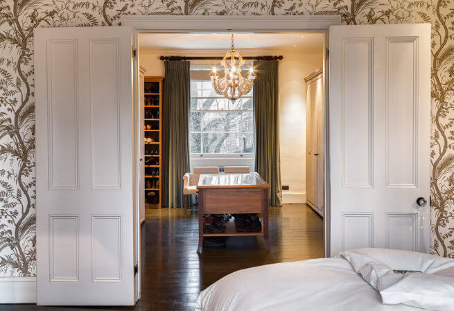 Double doors with original glass doorknobs lead to the spacious walk-in closet and dressing room. The beautiful crystal chandelier lends an air of sophistication and elegance to the space's functionality.