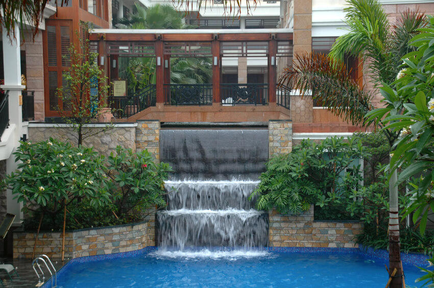 A three tier waterfall flowing into the swimming pool from beneath a bridge.