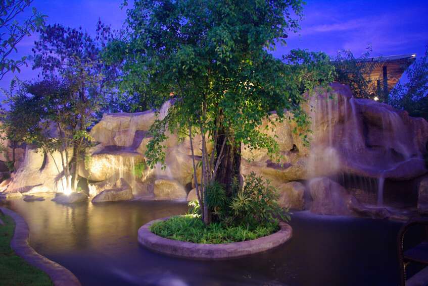A lighted series of artificial stone waterfalls with a center island with natural trees.