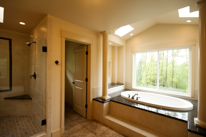 Multiple skylights working in unison with a tub-side picture window call this beautiful bathroom space their home. The bathtub encasement is topped with a dark stone for contrast, while a step leads the way for easy access.