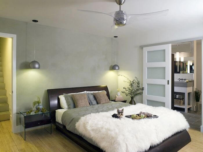 On the lowest level is the primary suite. The sleek curved bed frame is topped by silky bedding and a fuzzy blanket. Low glass-topped nightstands have hanging lights above them. A pocket door leads into the primary bathroom.