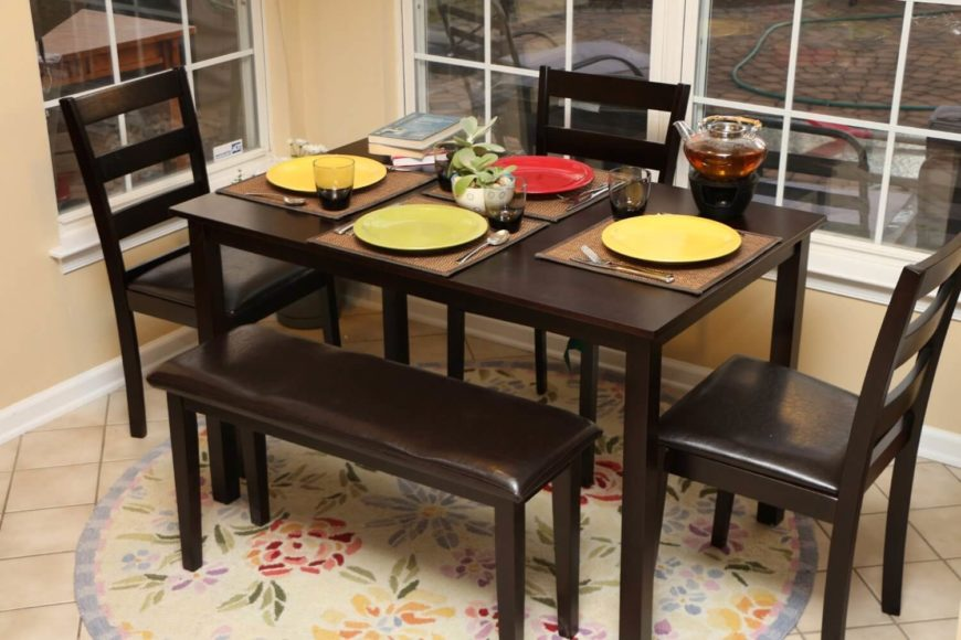 This sleek and simple dining table features a dark but warm wood tone and sharp-edged design with minimal fuss. This comes as a set with the pictured chairs and bench seating.