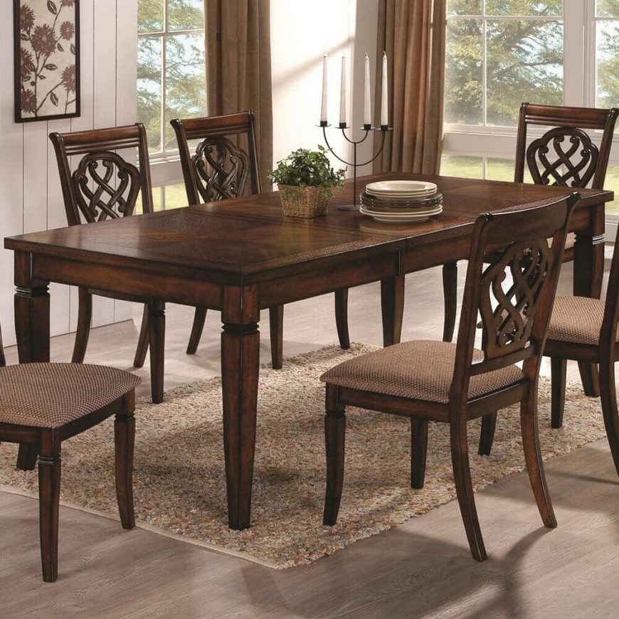 In contrast with the prior entry, this traditionally styled wood table features carved legs and a detailed, textural surface. Large leaf is seen inserted for expanded seating capacity.
