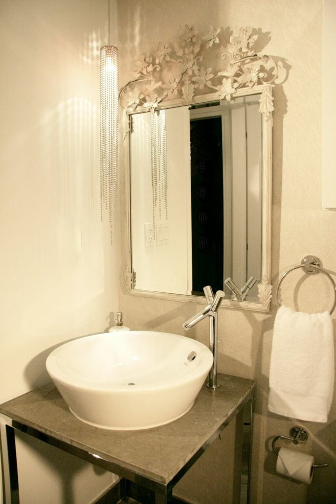 A smaller half-bath near the living room with a small metallic vanity with a sink that matches those in the full bathroom. The mirror has a delicate floral design out of wrought iron, and a small, thin crystal chandelier dangles slightly off to the left.
