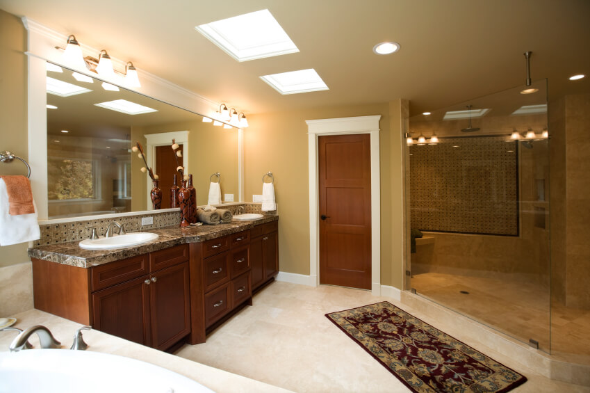This space, though rich in dark wood and ecru walls appears light and vibrant thanks to the strategically placed skylights, fixtures, and light tiled floors. A traditional area rug sits outside an attractive enclosed shower, and a gorgeous double vanity with a marble countertop offers plenty of space.