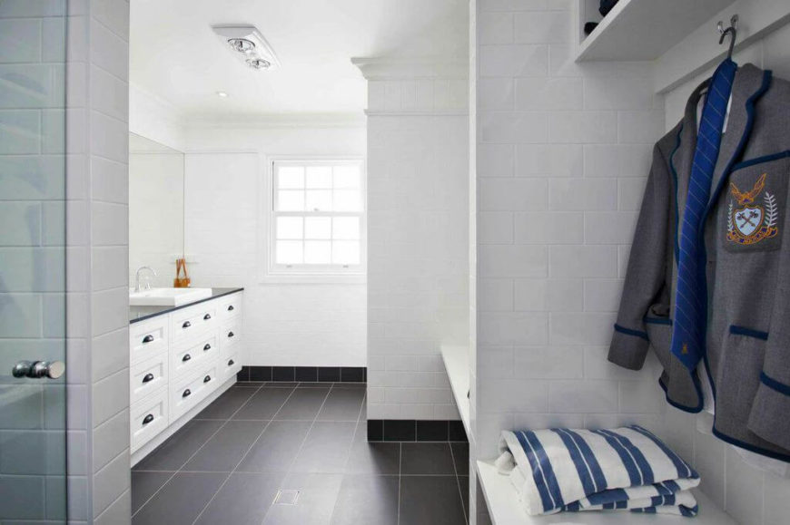 The main floor bathroom is all subway tile, with a row of black contrasting tiles as the white walls meet the charcoal gray flooring. The full bathroom also doubles as a mudroom, with two areas with benches and hooks for hanging jackets. The shower is perfect for a quick rinse after swimming in the backyard pool.