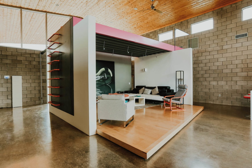 "Here we see the ""stage for living,"" a three-walled room secluded in the center of the open space. Raised platform wood flooring and steel beam ceiling frame the space, with a ladder on the side for easy access to the upper level."