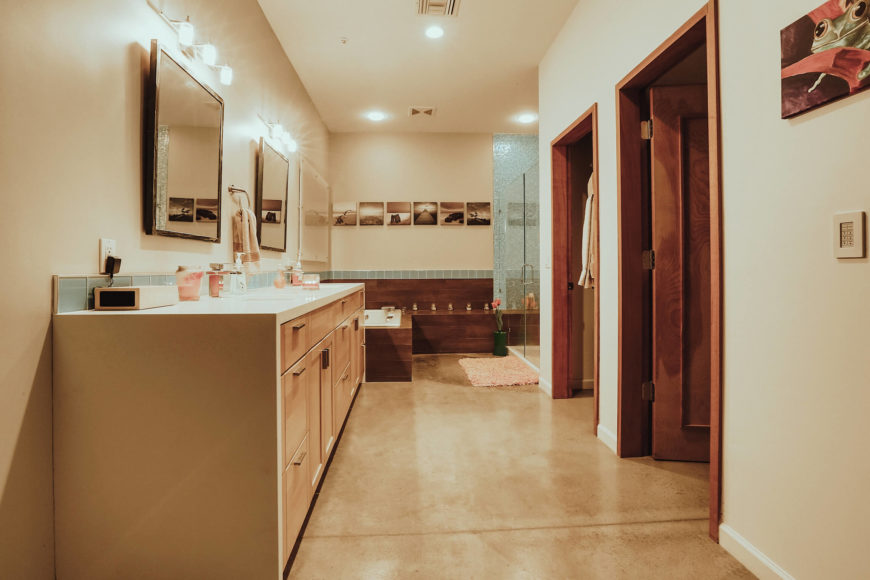 This second, larger bathroom features a lengthy traditional double vanity with minimalist wood drawers and white countertop. Bath area can be seen at far end.