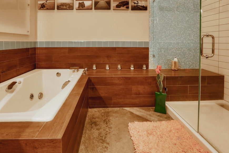 Closer view reveals an expanse of rich wood paneling surrounding the bath and leading into the walk-in shower. The subtle addition of blue tile adds variety of detail.