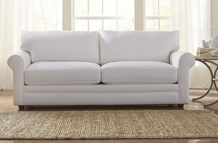 Here we have a plush all-white sofa, with roll-arms and short wooden legs. The low-slung body and wide back make for extra comfort.