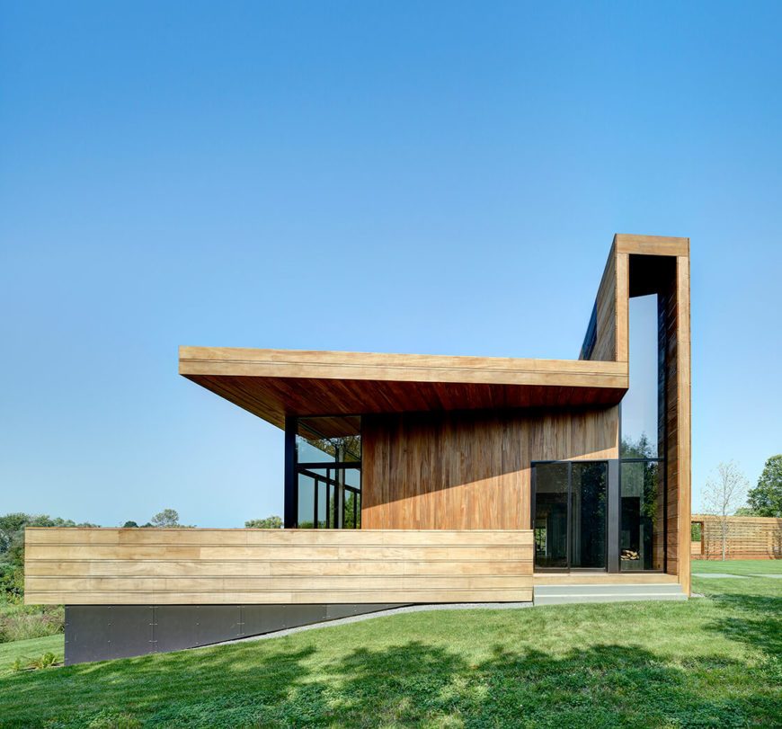 Seen from the side, the main house structure is a series of elevated horizontal forms, with a large two story wall soaring above the main part of the roof. Extensive glass makes for excellent natural lighting and an open appearance.