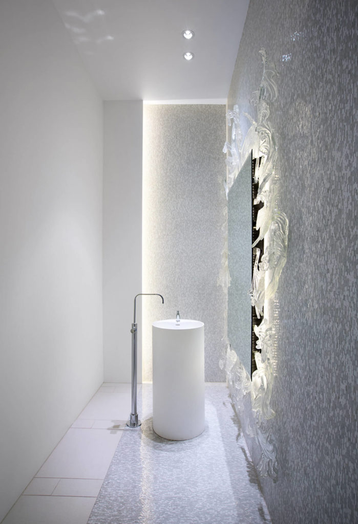 The bathroom features this extraordinarily unique sink, with large floor-mounted faucet leaning over a white cylinder pedestal. Micro-tile walls highlight the glass-framed mirror at right.