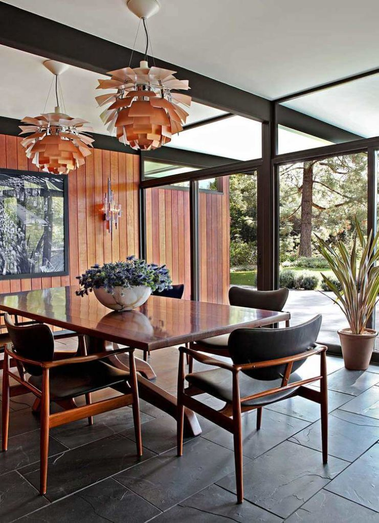 At the other end of the open space, we see the dining room, housing this large, unique dining table and set of leather upholstered chairs. A pair of paper-feathered chandeliers hangs above.