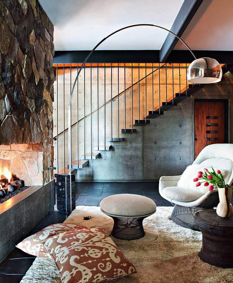 A chrome arched floor lamp illuminates this living room offering a stone fireplace facing comfy seats and coffee tables that sit on a beige shaggy rug.