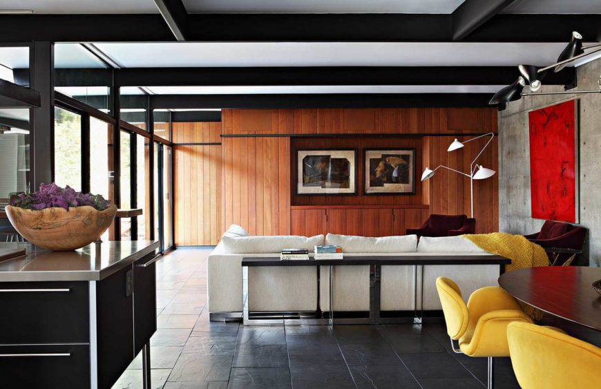 The living room houses a sparkling mixture of elements, from dark stone flooring to bright redwood and neutral concrete walls, to chrome and black tables and storage.