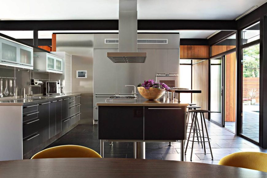 Modern palette L-shaped kitchen with gray drawers, breakfast island, black tiles floors, and glass sliding doors.