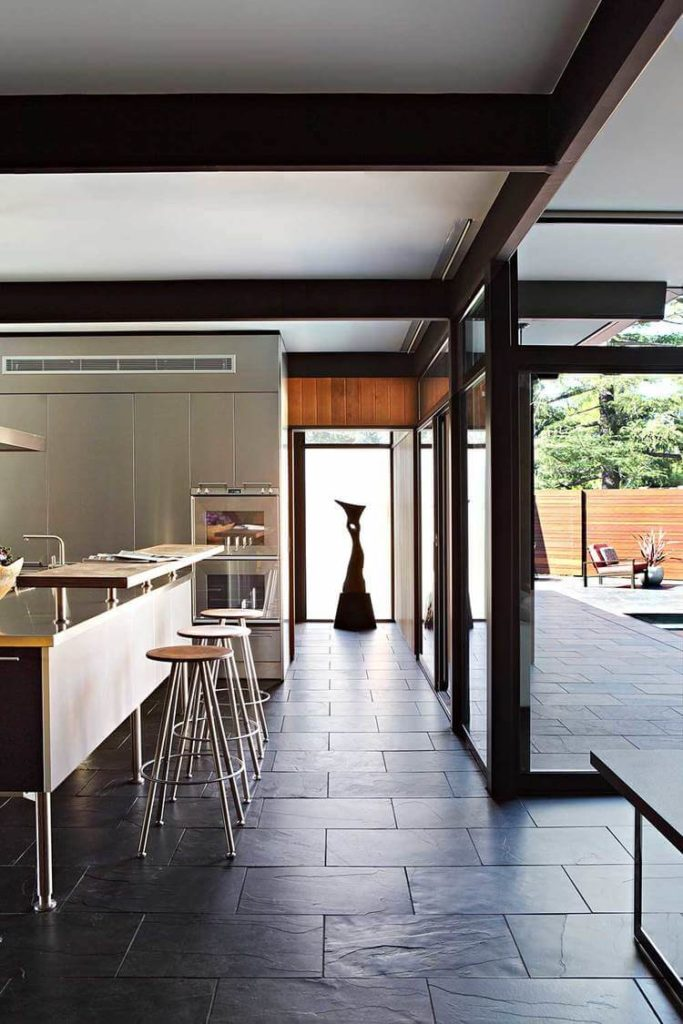 The kitchen is fully illuminated during day by the wraparound glazing. Here we see the barstool dining area overlooking the expansive patio at right.