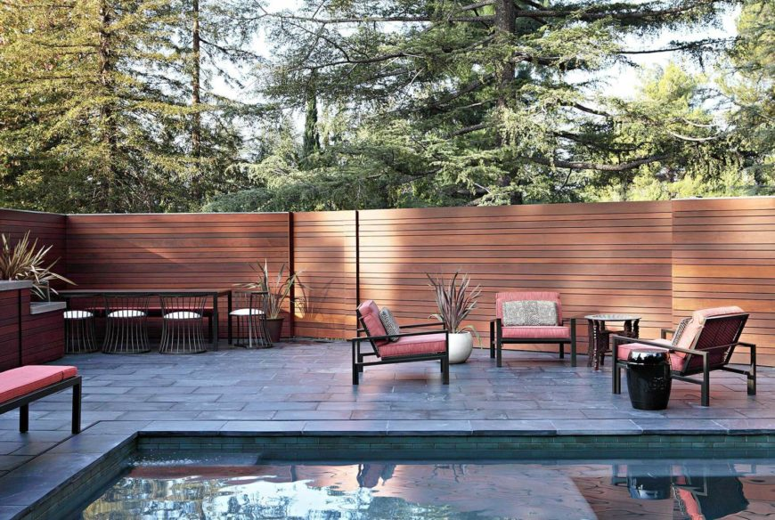 The patio continues the stone tile from within the house, expanding to a tall seamless timber fence. Various arrays of seating surround the swimming pool.