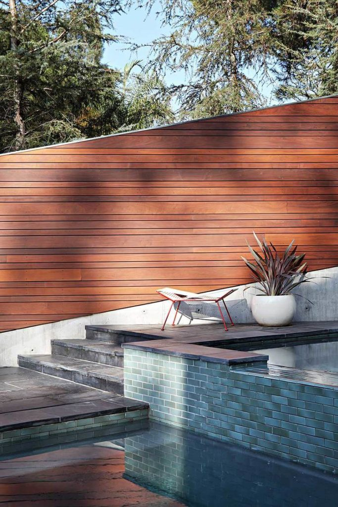 Here's a close view of the cool blue tile wrapping the pool space, contrasting sharply with the rich warm wood tones of the fence.