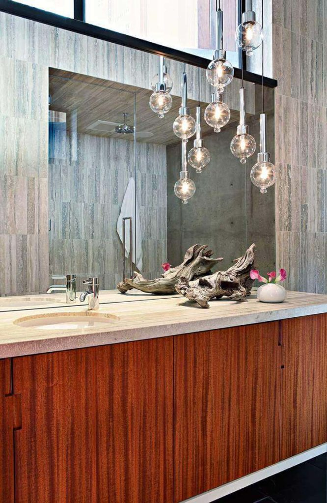 This bathroom features rich wood panel cabinetry beneath a marble vanity countertop. An array of open-bulb pendant lights creates a unique chandelier effect.