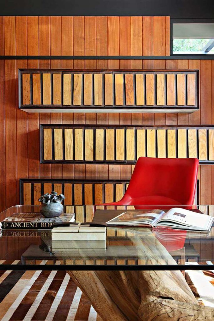 The walls feature floating wood-paneled shelving, seen here over the massive expanse of glass and bright red leather office chair.