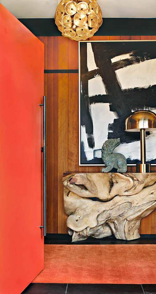 Moving into the private bedroom spaces of the home, bright orange is introduced to the color palette. Another knotted wood piece here forms a side table, surrounded by art.