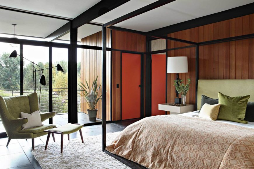The primary bedroom houses a large four-poster bed with a black metal frame matching the structure of the house. A small private balcony extends through full height glass at left.