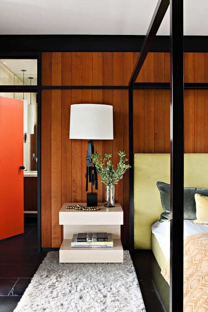 A minimalist, two-tiered bedside table stands beside the lime green headboard, with orange door at left.
