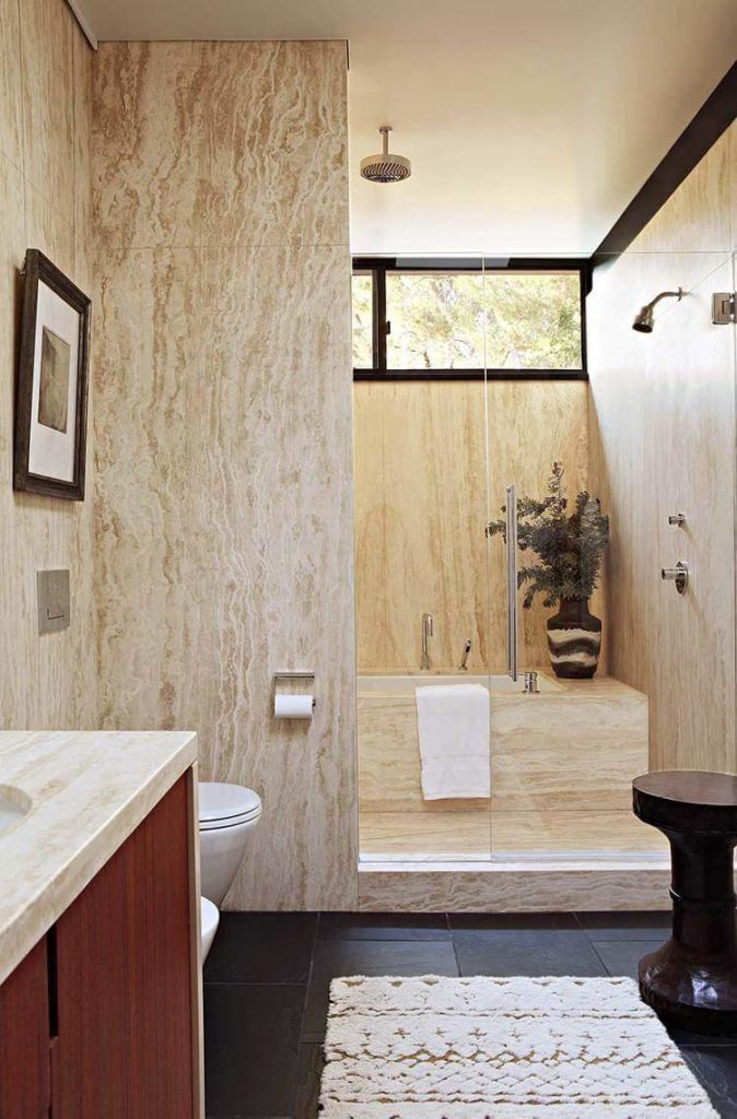 Beige marble fills the room, including this immense walk-in shower enclosed in glass, housing a soaking tub.