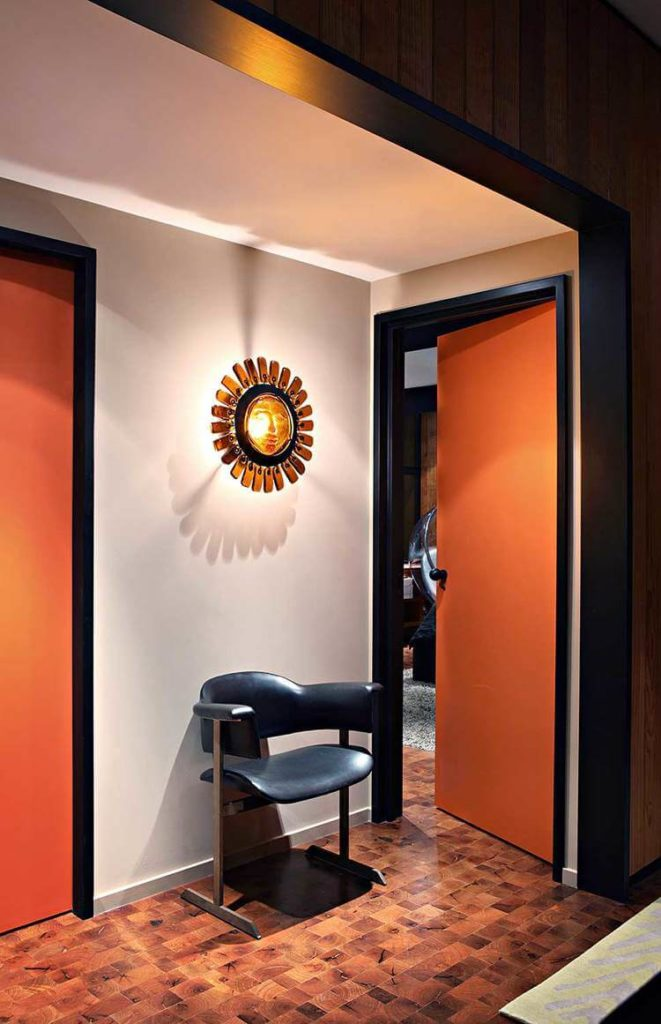 Moving toward the bedrooms, we see white walls and orange doors contrasting with the hardwood flooring. A black leather chair stands beneath a glass sun sculpture between two rooms.