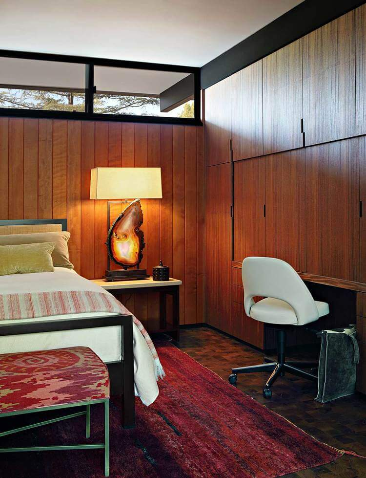 Mid-century modern primary bedroom with tiles flooring topped by a large area rug and is surrounded by rustic walls lighted by warm white lighting.