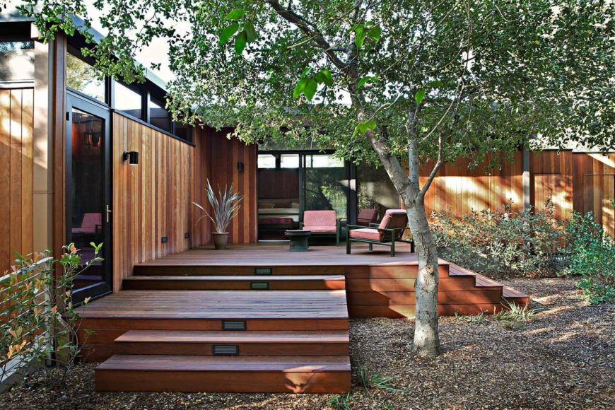 The sprawling home has room for a second, smaller patio. This space is wrapped in vegetation, with direct access from the bedrooms.