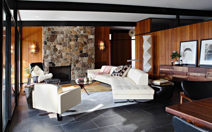 The open design living room houses an array of contemporary furniture, including white sofa and club chair, contrasting with the natural building materials surrounding. The large format stone tile flooring creates an earthy anchor for the space.