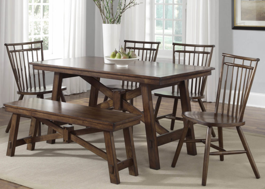 This rustic-look dining table features loose A-frame structure beneath its two-layered surface. Exposed bolts and a dark finish make for a rich and old fashioned dining table.