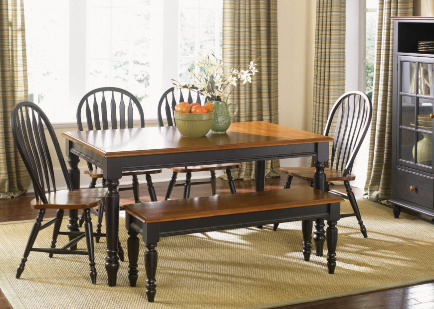 This rich, high contrast table features natural wood tone surface and dark painted legs, with a carved, high polish veneer. The interplay of sharp angles and curved surfaces makes for a lot of detail.