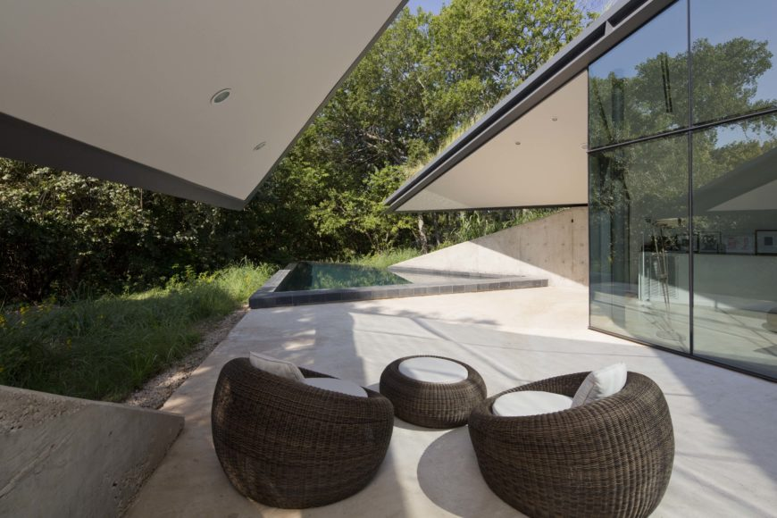A simple patio setup consisting of a trio of spherical wicker chairs stands next to the triangular pool marking the edge of the structure. Roof overhangs provide shade and privacy, controlling temperature.