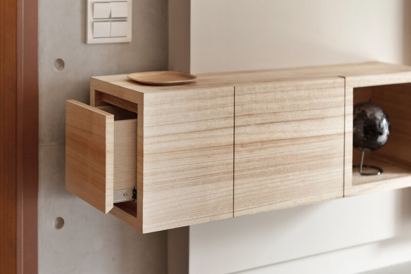 Here's a detail view of a unique wall-mounted shelf in the living room. A simple cubic structure hides a drawer for useful items like keys.