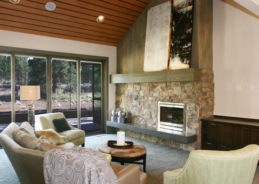 The home's open foyer opens up directly into the great room, which has soaring ceilings and a large enclosed fireplace with a stone and wood hearth and mantle.