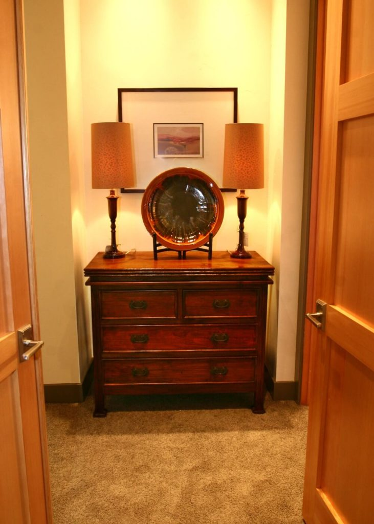 The entrance to the walk-in closet from the primary bedroom has a small nook that contains a beautiful antique dresser.