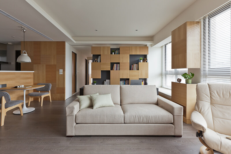 The open living room centers on this beige sofa, backed against a dark toned wood desk. In the background we see the cubic shelving unit.