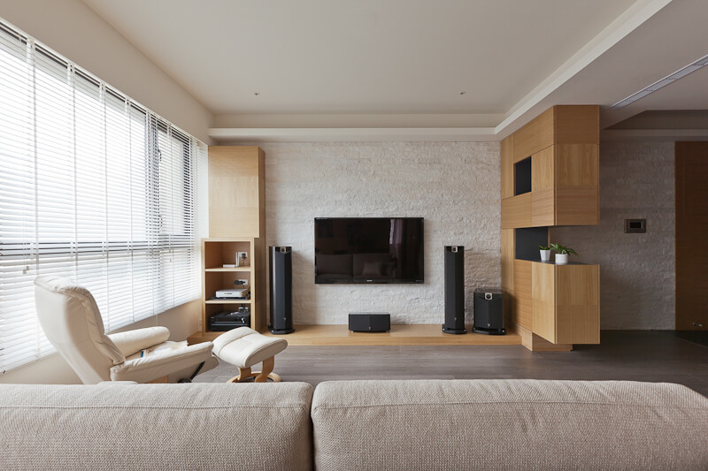 The entertainment shelving against the white brick wall stands a pair of shelves around a low-slung wood panel holding the AV equipment. Shelf on the right divides the living room from the rest of the home.