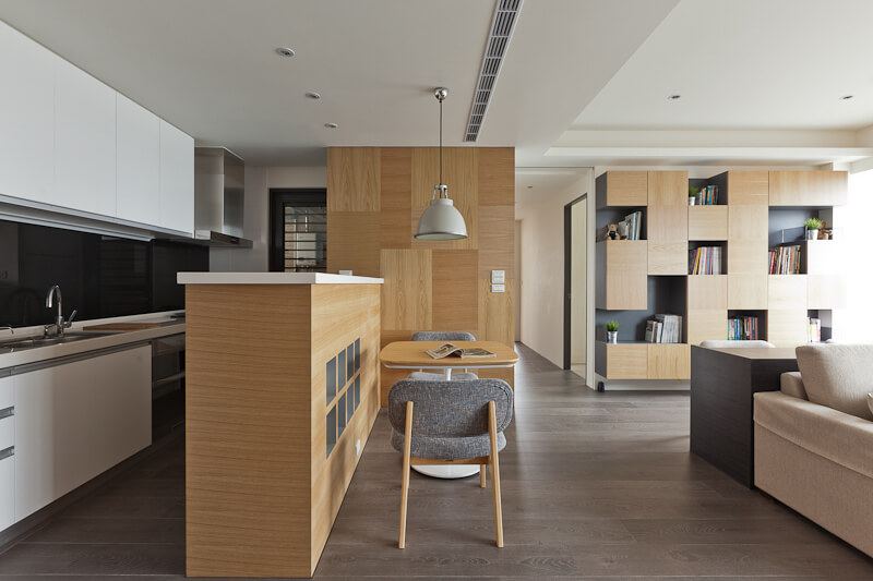 The kitchen is defined by the large light wood island at left, and small dining table at center.