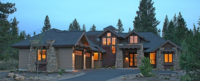 Exterior of the rustic home of wood and stone with a sprawling design.