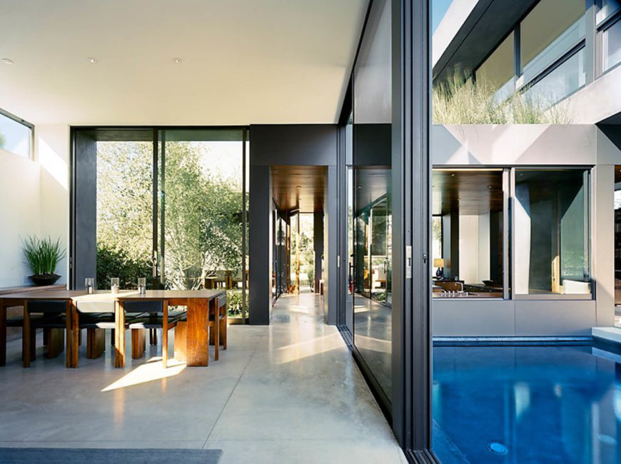 Starting in the open plan dining and living room, we see in every direction throughout the house via full height glass. Natural wood dining table contrasts with the sleek surroundings.