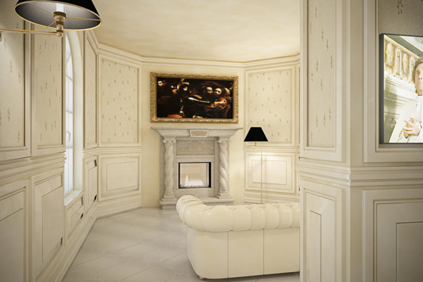 Moving around the central wall, we see a white leather, button tufted sofa facing a fireplace flanked by marble pillars.