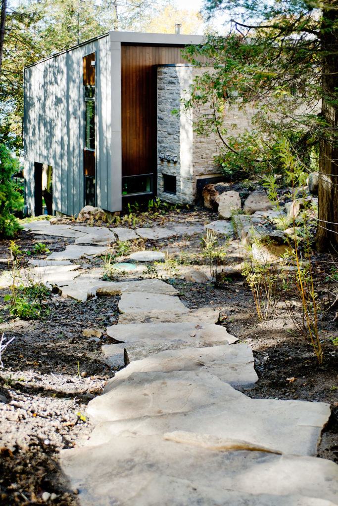 Moving further back, we see the broken stone path leading down toward the home from street level, with the stone, timber, and metal exterior visible at once.