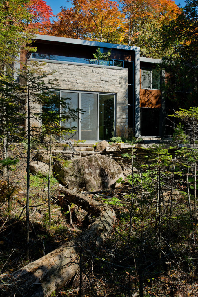 Here we see the home from the lake side, surrounded by large stones and forest, rising out of the environment.
